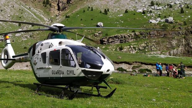 Helicóptero en el que fue evacuado el senderista. Al fondo, mientras era atendido en el lugar donde tuvo el encontronazo con las vacas de montaña, habitualmente pacíficas