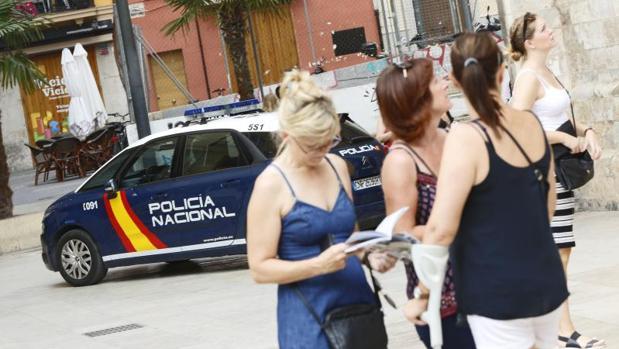 Varias mujeres junto a un coche patrulla de la Policía Nacional en Valencia