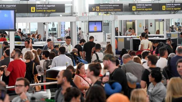 Decenas de pasajeros, esperando para pasar los controles, este viernes en El Prat