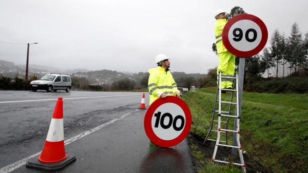 Operarios colocan una señal de tráfico en una carretera gallega