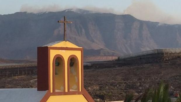 Una iglesia en Agaete con Tamadaba al fondo ardiendo