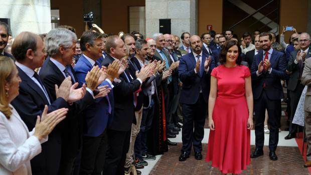 Isabel Díaz Ayuso, con Pablo Casado detrás de ella, ayer en Sol