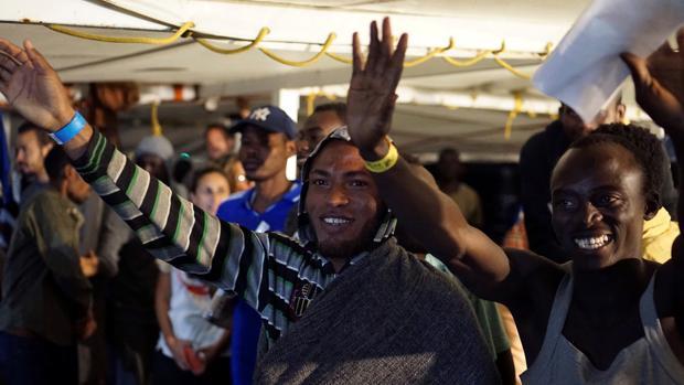 Los migrantes que quedaban a bordo del barco saludan momentos antes de desembarcar en la isla de Lampedusa