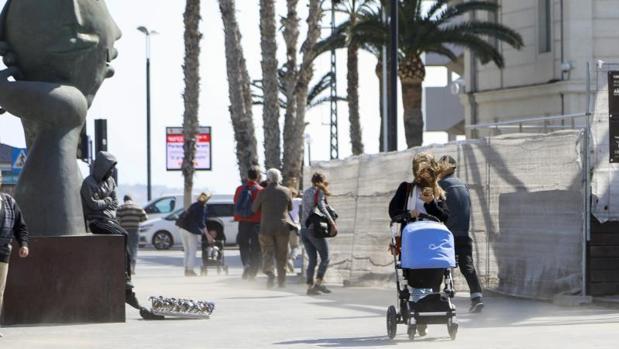 Transeúntes se protegen del mal tiempo en Alicante