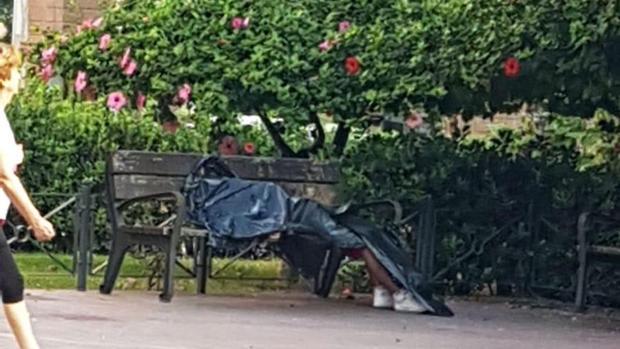 Una mujer pasa junto al cadáver del hombre en la plaza de Joaquín María Lopez de Alicante