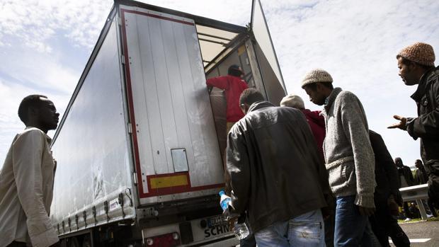 Inmigrantes suben a un camión en dirección al Reino Unido en Calais, en 2015