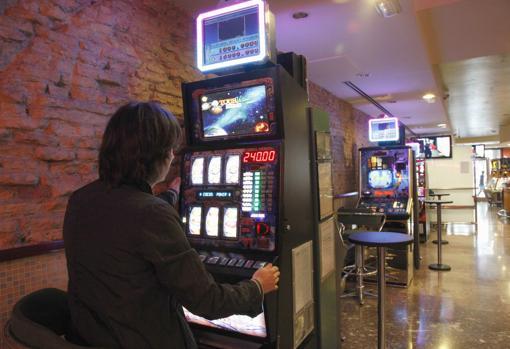 Un joven juega en una máquina tragaperras en un salón de juegos