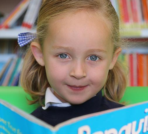 Alumna de Infantil de Caxton College leyendo en la biblioteca de este centro británico