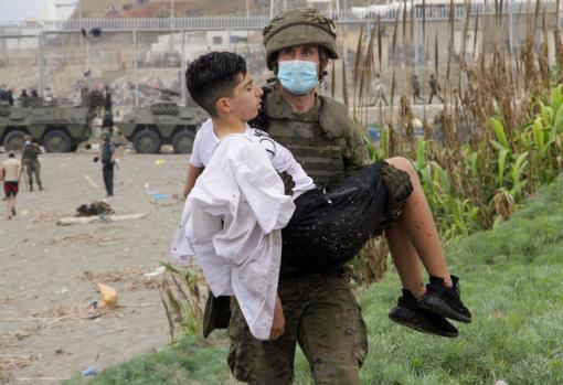 Un soldado del Ejército de Tierra ayuda a un inmigrante que ha logrado cruzar uno de los espigones fronterizos de Ceuta