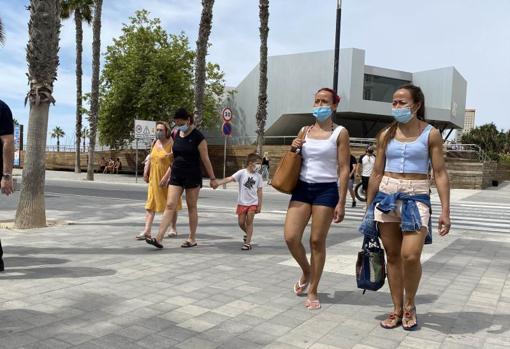 Paseantes en las inmediaciones de la playa del Postiguet de Alicante
