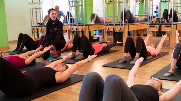 Una profesora de pilates, dando pautas para practicar un ejercicio.