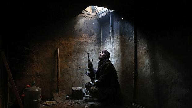Un combatiente de la oposición siria se protege del fuego enemigo en Arbeen, la zona bajo su control a las afueras de Damasco