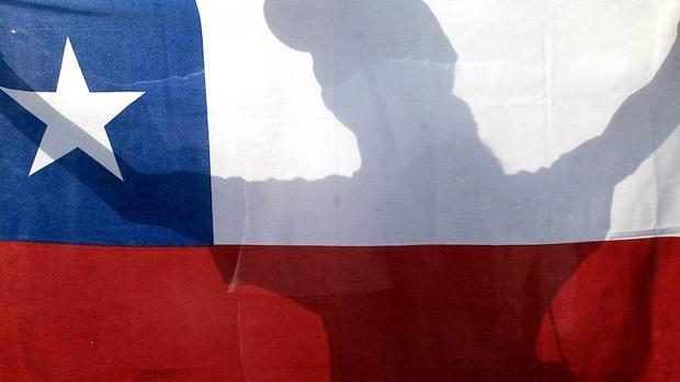Una mujer sostiene una bandera de Chile