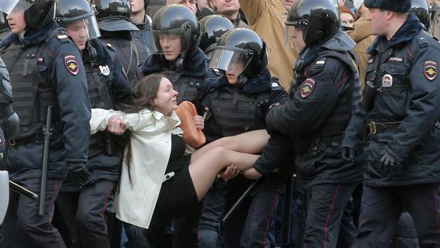 Policías antidisturbios rusos detienen a una manifestante durante las protetas convocadas por la oposición en el centro de Moscú