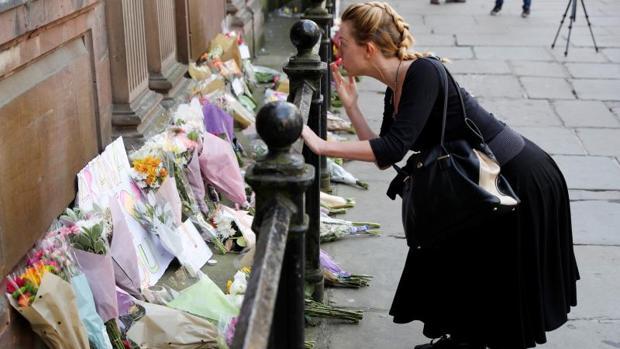 Una mujer lanza un beso tras depositar unas flores en un memorial por las víctimas del atentado de Mánchester