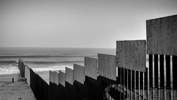 Dos personas pasean junto al muro fronterizo que separa México y Estados Unidos en Tijuana