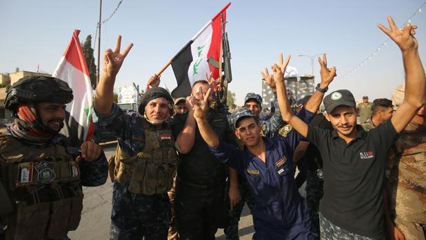 Miembros de la policía federal de Irak hacen el signo de la victoria tras la toma de Mosul el pasado julio