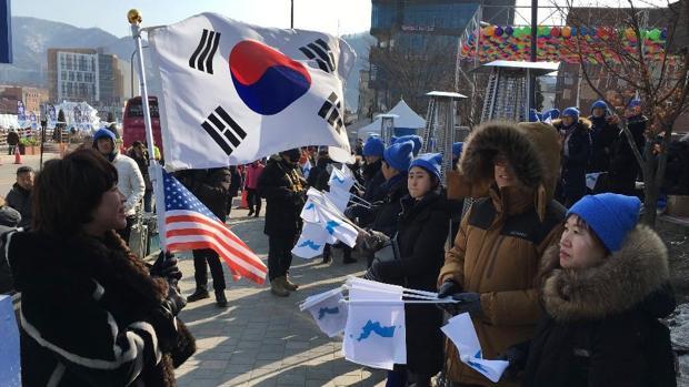 Con la bandera surcoreana (a la izquierda), los detractores de Kim Jong-un se manifiestan ante quienes piden la reunificación en los alrededores del Estadio Olímpico de PyeongChang