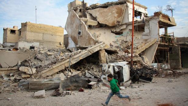 Un niño corre frente a los restos de un edificio tras los bombardeos en Guta oriental, a las afueras de Damasco
