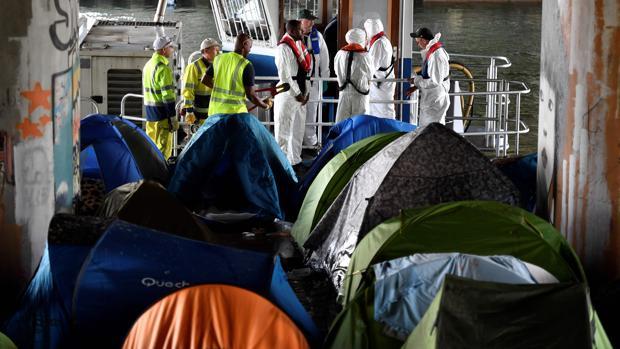 Los trabajadores llegan para limpiar el campamento improvisado de inmigrantes Millenaire a lo largo del Canal de Saint-Denis cerca de Porte de la Villette