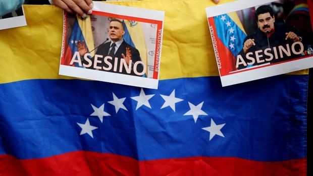 Vista de fotografías del presidente de Venezuela Nicolás Maduro y del fiscal general Tarek Saab en las que se lee la palabra «Asesino»