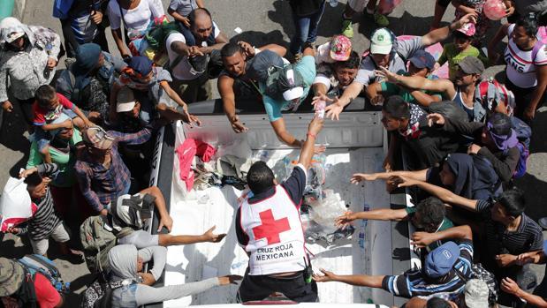 Personal de la cruz roja entrega agua a migrantes hondureños que continúan recorriendo otro tramo del territorio mexicano
