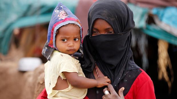 Una niña transporta a un niño en un campamento para desplazados en Yemen