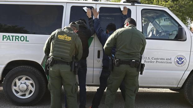 Una patrulla cachea a dos detenidos en la frontera, en 2017