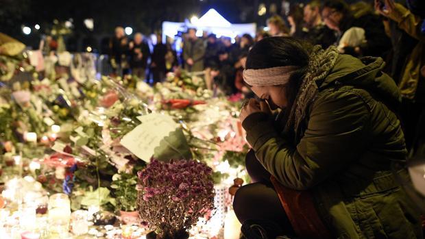 Una mujer reza por las víctimas del ataque terrorista del 13 de noviembre de 2015 en París