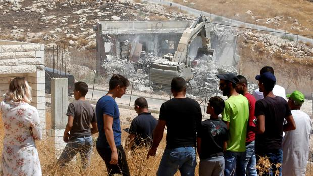 Vecinos de la zona palestina de Wadi Humus observan la demolición de una vivienda