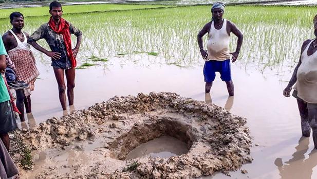Habitantes del pueblo de Mahadeva posan al lado del cráter creado por el aterrizaje del supuesto meteorito