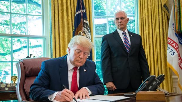 El presidente de Estados Unidos, Donald Trump, firma frente al vicepresidente, Mike Pence