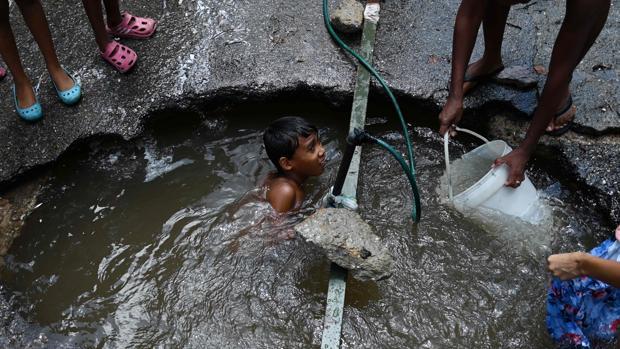 Un niño se baña en una poza en una calle de Caracas, el pasado mayo