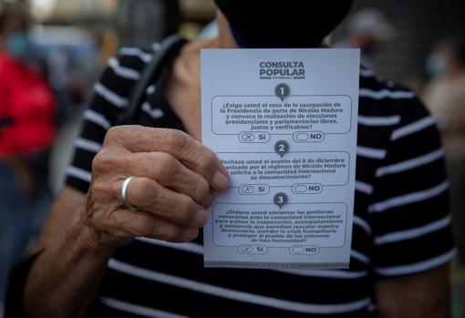 Una mujer sostiene una ficha con las tres preguntas de la consulta