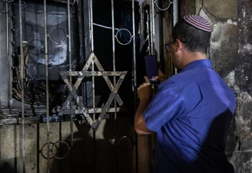 Un hombre israelí mira una sinagoga incendiada en los enfrentamientos en Lod
