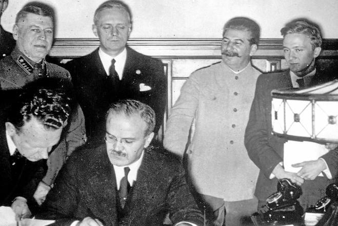 Stalin (segundo por la izquierda) sonríe junto al ministro ruso de Exteriores, Vyacheslav Mólotov, mientras firma el ministro alemán, Joachim von Ribbentrop