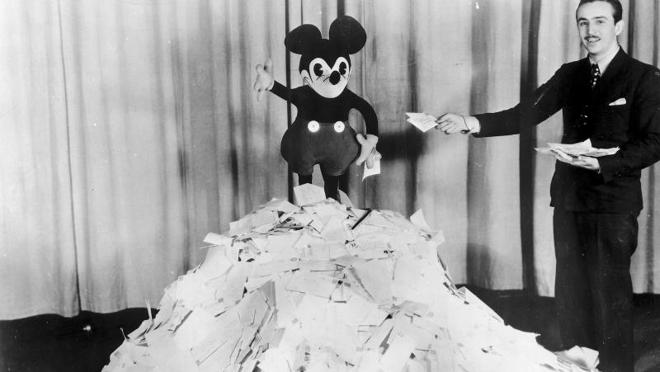 Walt Disney posando con una pila de las 10.000 cartas que recibía Mickey Mouse a diario