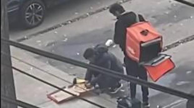 Imagen de los dos repartidores comiéndose parte del pedido