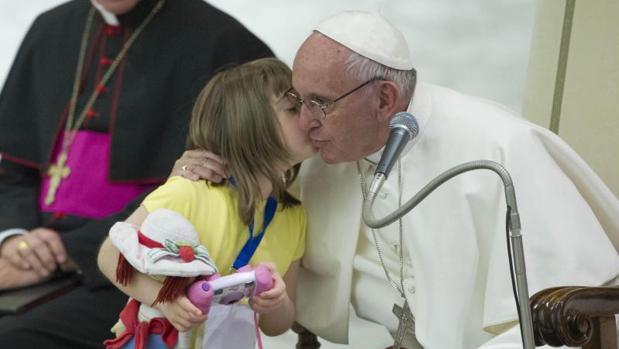 El Papa saluda a una niña con sindrome de Down durante un encuentro con personas con discapacidad