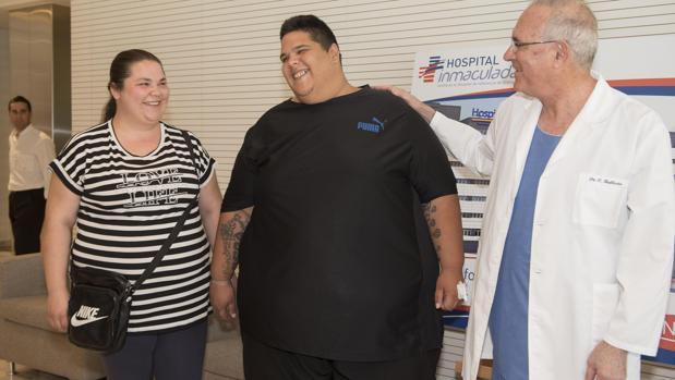 Juan Manuel Heredia (c),, el hombre más obeso de España que este año ha llegado a pesar 300 kilos, acompañado de su esposa y del doctor Carlos Ballesta, momentos antes de someterse a la intervención de un novedoso bypass gástrico por laparoscopia para combatir su obesidad extrema