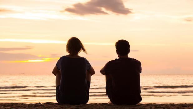 Una pareja mira el atardecer desde una playa
