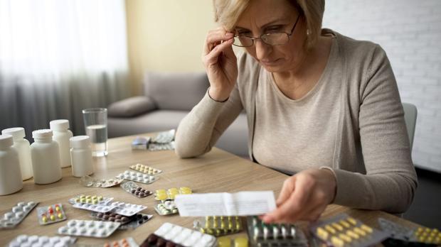 Una mujer consulta el prospecto de los fármacos que le han prescrito