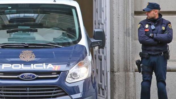 Imagen de un coche y un guardia de la Policía Nacional