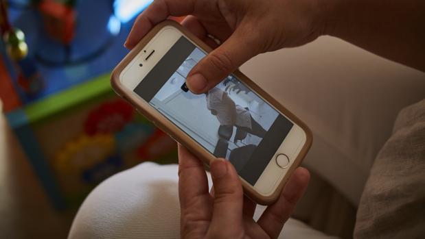 Una mujer muestra la foto de su gestante embarazada