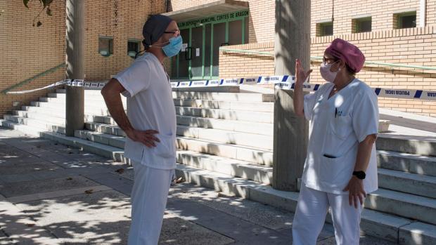 Dos sanitarios conversan ayer en las inmediaciones del polideportivo Cortes de Aragón de Fraga, donde hay algunas personas que han dado positivo