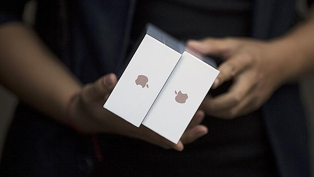 Un empleado de Apple con las cajas de los últimos terminales de la compañía, iPhone 6S y 6s Plus