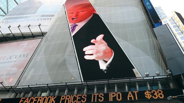 Una imagen de Donald Trump preside una pantalla digital en donde se muestran datos bursátiles